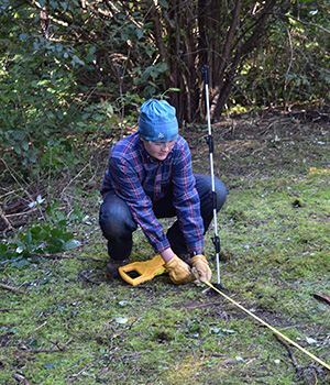 An adolescent Montessori student takes measurements in the natural environment.