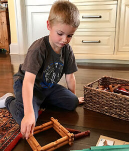 A child uses his imagination while building a structure with wooden Lincoln Logs
