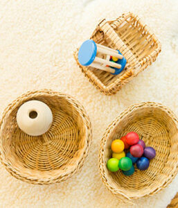 Small baskets with colorful wooden toys can be found in a Montessori home.