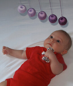 An infant holding a metal rattle lies beneath a mobile in a Montessori-inspired bedroom.