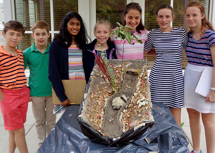 A group of Montessori elementary students create a a model of a river bed out of clay and other natural materials.