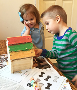 Two young children work together on painting a birdhouse