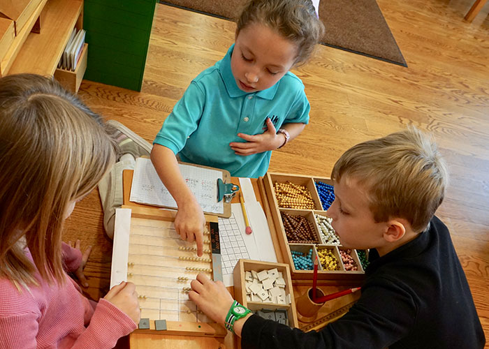 Three students in a Montessori Elementary classroom use tangible math materials to learn new concepts
