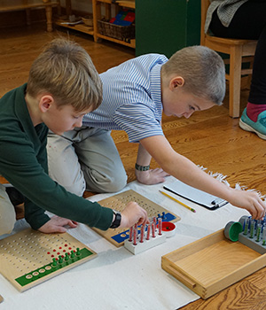 Two students in a Montessori classroom work together using racks and tubes to solve a math problem