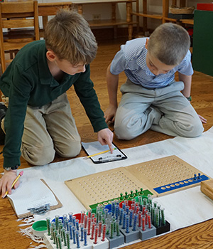 Montessori students check their work to find an error