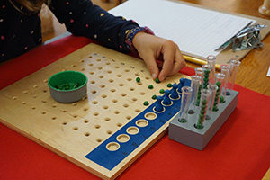 A child in a Montessori classroom sets up a math problem using the racks and tubes.