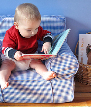 An infant sits in a low, soft chair and looks at a picture book in his bedroom