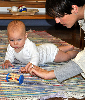 An infant lies on a rug with her mother and scoots toward a wooden toy