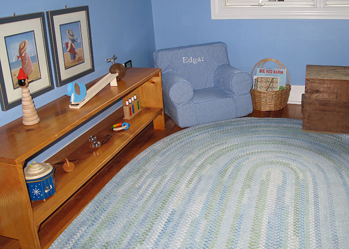 A Montessori bedroom includes a low shelf for infant toys, a rug, a basket for books, and room to move.