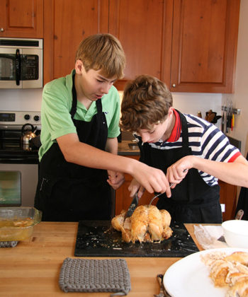 Students in a Montessori Secondary classroom carve a chicken in preparation for a communal meal