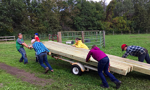 Montessori Secondary Level students work together to haul lumber on a service learning trip