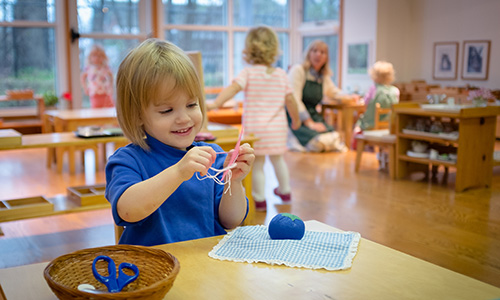A child in a Montessori Young Children's Community sews independently