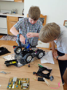 Students in a Montessori classroom build an electric car together