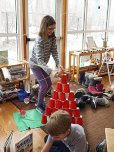 A student in a Montessori classroom builds a structure using plastic cups