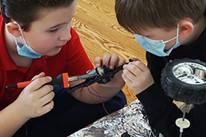 Students in a Montessori Upper Elementary class use a soldering gun to construct an electric car