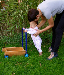 A young child learning to walk pushes a cart in the grass with her mother nearby