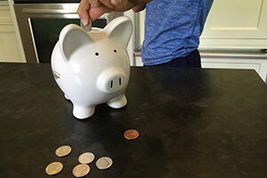 A child inserts a quarter into the top of a piggy bank