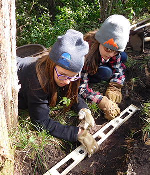 Adolescents work together outdoors with carpentry tools