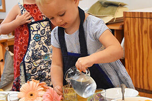 A child in a YCC pours water from a glass pitcher into a small glass