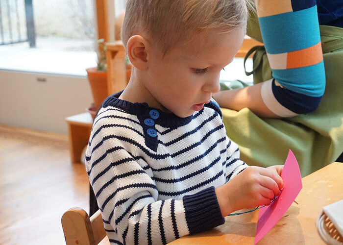 A child in a Montessori YCC uses fine motor skills to sew