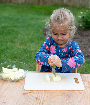 A young child independetly cuts an apple
