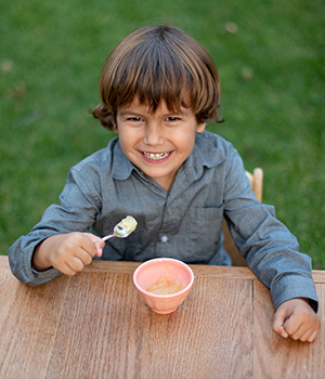 A child enjoys eating homemade applesauce