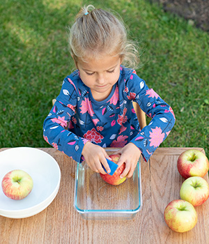 A child washes an apple in preparation for making applesauce