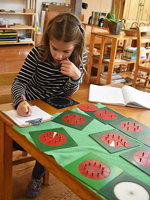 A child in a Montessori Elementary classroom works with the Metal Triangles