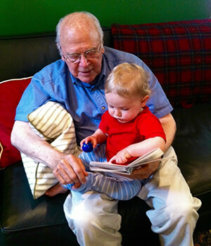 A grandfather reads aloud to his young grandson on his lap