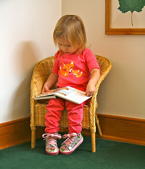 A young child quietly lookd through a book at home