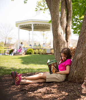 An elementary aged child reads for pleasure under a tree