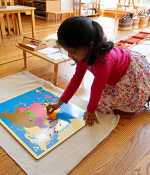 A Montessori students works with a puzzle map of Asia