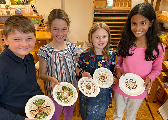 Montessori students display the rangoli art they made with the help and direction of a classmate who taught them about the traditional Hindu art form