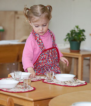 A young Montessori child sets the table for a communal meal