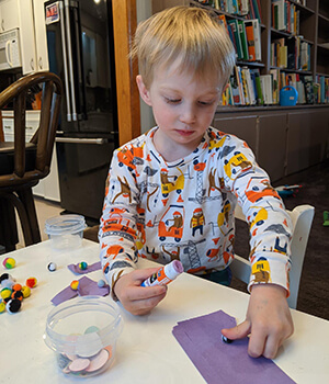 A young child works on a gluing art activity at home