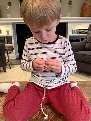 A child strings beads during quiet time at home