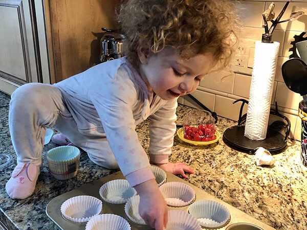 A toddler helps prepare muffins at home