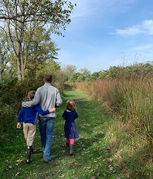 A father walks with his children in a nature preserve