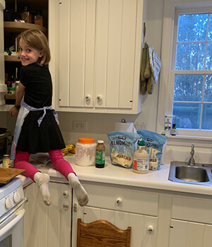 A child bakes in her kitchen during Montessori homeschool