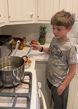A Montessori child hard boils eggs on the stove