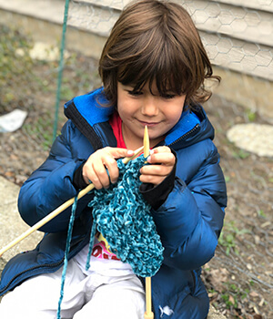A Montessori child knits at home