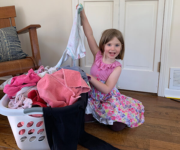 A Montessori child sorts laundry for her chores routine