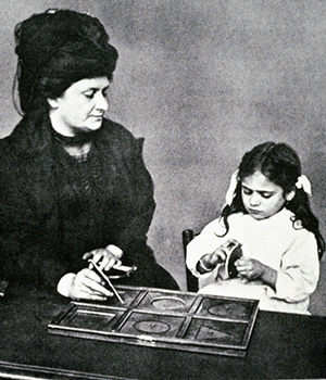 Maria Montessori observes a child working with metal insets