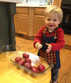 A young child scrubs potatoes at home