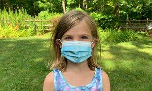 A child wears a disposable surgical mask