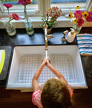 A Montessori child practices hand washing before returning to school