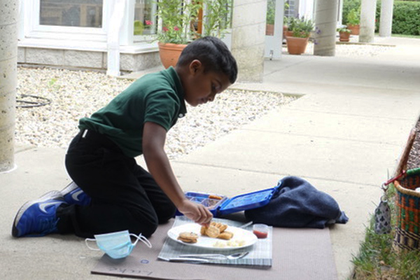 A Montessori child eats the lunch he made himself
