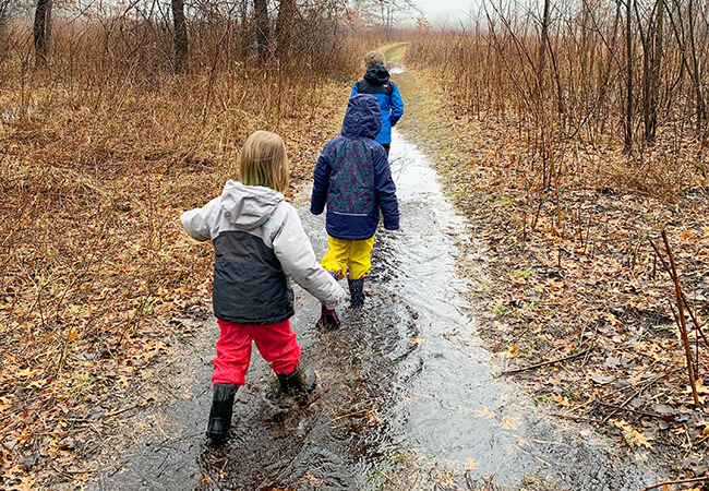 Children walk on a flooded path in the forest preserve