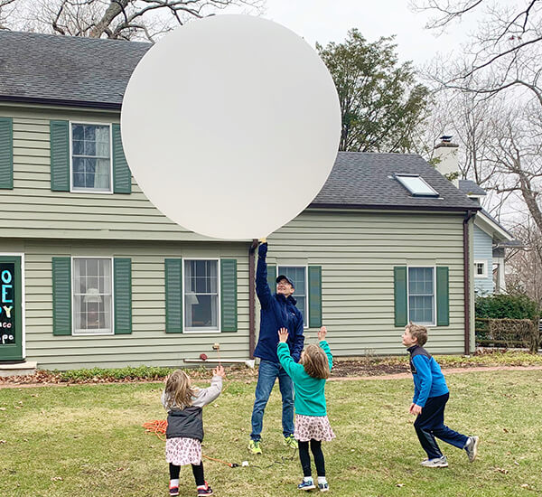Children watch with joy as their father lifts a giant balloon over his head
