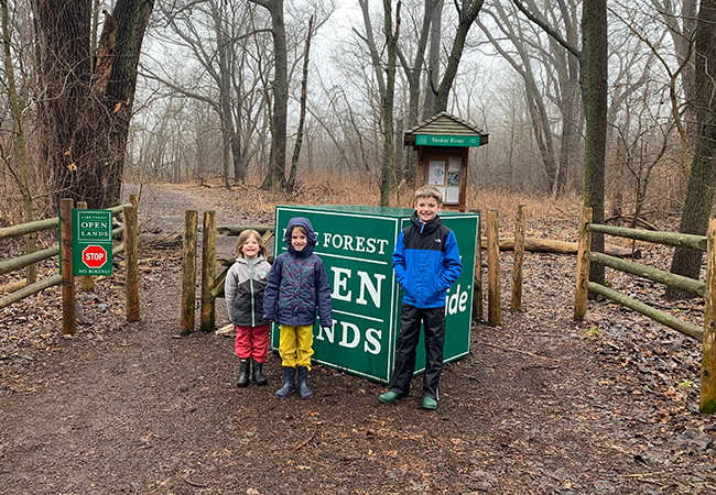 Children stand at the beginning of a trailhead at a local nature preserve